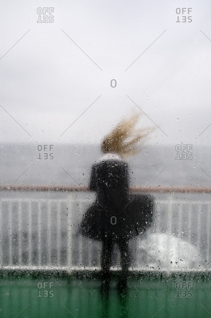 Sweden, Rear view of young woman behind wet window
