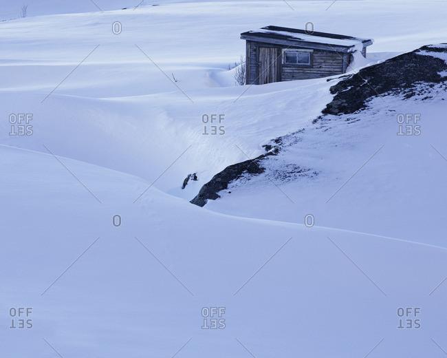 Sweden, Lapland, Riksgransen, Wooden shed in snowy landscape