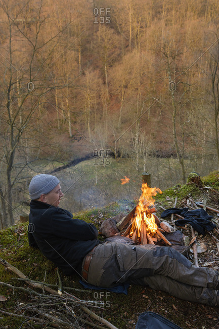 Sweden, Skane, Man lying down by campfire