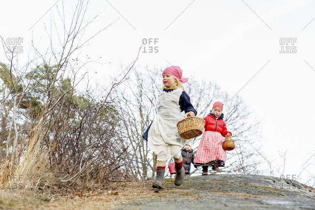 Sweden, Sodermanland, Children (2-3, 4-5) running with baskets
