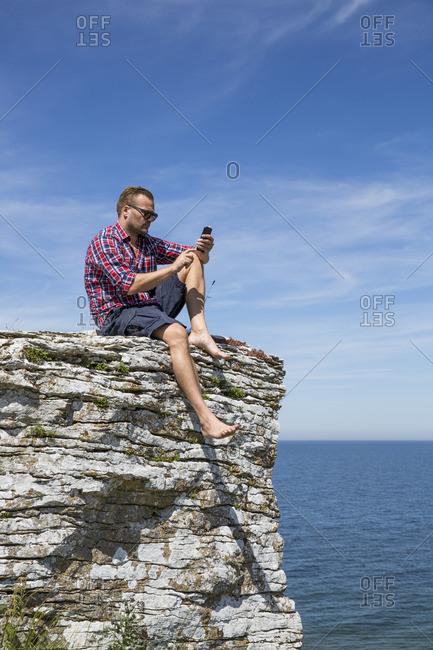Sweden, Gotland, Mature man sitting on cliff at seashore and using telephone