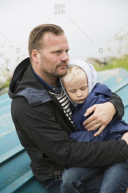 Sweden, Gotland. Mature man sitting on boat turned upside down and holding boy (6-7)