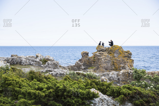 Sweden, Gotland, Mature man and boys taking pictures on rock at seashore