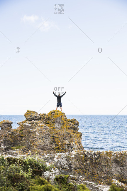 Sweden, Gotland, Mature man standing on rock at seashore with arms raised
