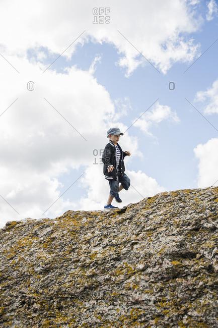 Sweden, Gotland, Boy walking on top of cliff
