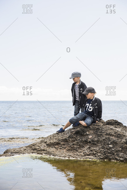 Sweden, Gotland, Boys on rock in sea