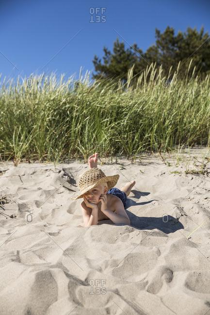 Sweden, Gotland, Boy in straw hat lying on beach