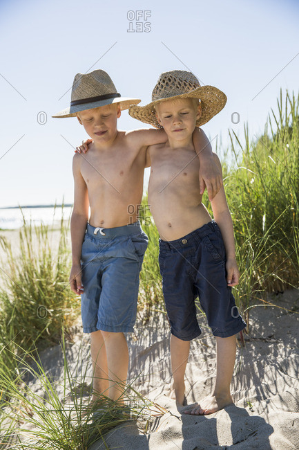 Sweden, Gotland, Shirtless boys in straw hats standing on sand dune at seashore