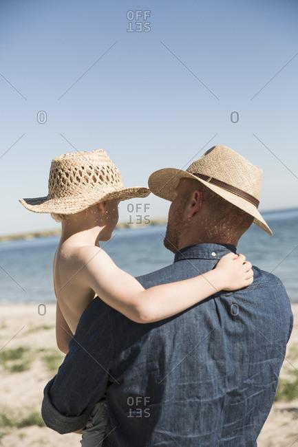 Sweden, Gotland, Mature man holding boy at seashore