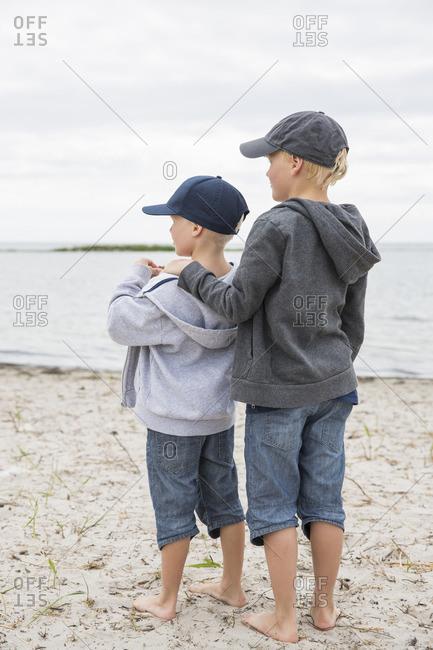 Sweden, Gotland, Boys in baseball caps standing at beach