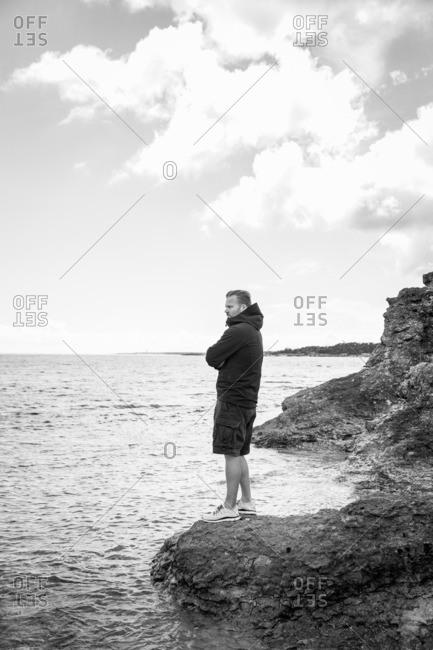 Sweden, Gotland, Mature man standing at rocky seashore