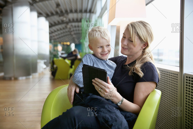 Germany, Hamburg, Mature woman sitting at airport hall and using tablet with boy sitting on her lap