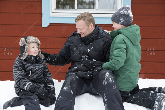 Sweden, Dalarna, Salen, Mature man and boys (6-7, )sitting on snow next to wooden cottage wall