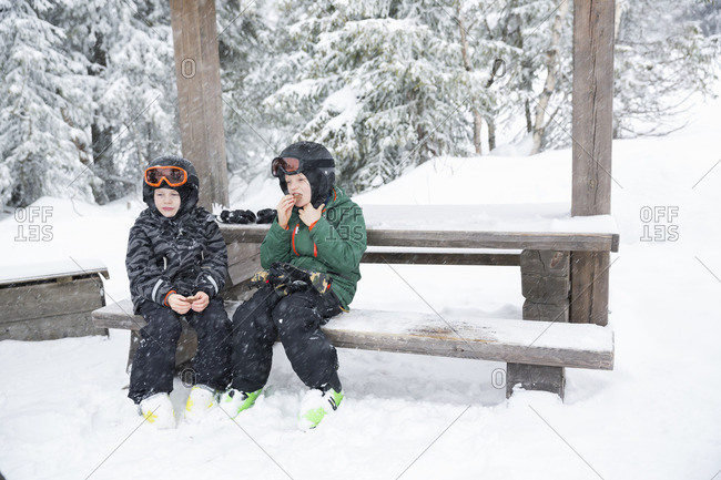 Sweden, Dalarna, Salen, Boys wearing helmets and goggles sitting on bench surrounded by winter landscape