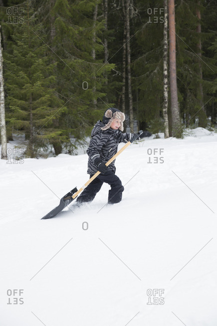 Sweden, Dalarna, Salen, Boy walking through snow by coniferous forest and carrying shovel