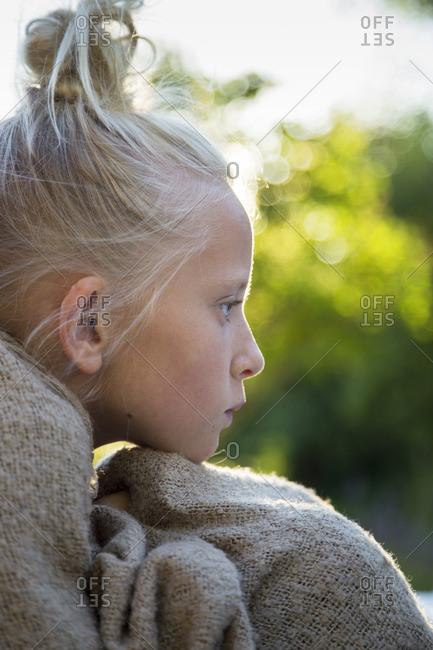 Sweden, Portrait of pensive girl wrapped in blanket
