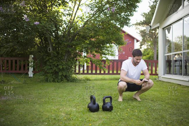 Sweden, Norrland, Vasterbotten, Mature man crouching next to weights on lawn in backyard