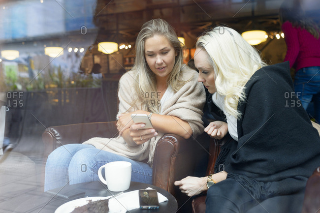 Sweden, Young women using mobile phone at cafe