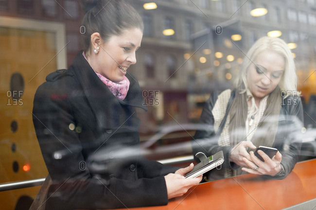 Sweden, Young women using mobile phones at cafe