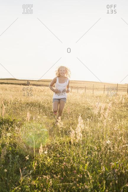Sweden, Skane, Teenage girl (14-15) running through meadow