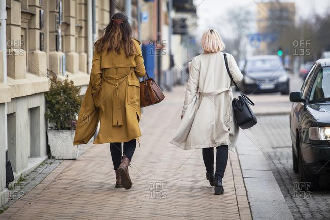 Sweden, Skane, Kirstianstad, Rear view of two women walking on street