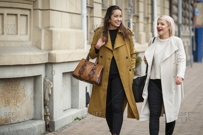 Sweden, Skane, Kirstianstad, Two young women walking on street