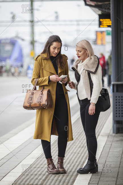 Sweden, Skane, Kirstianstad, Two young women standing with smartphones at train station