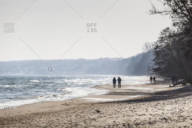 Sweden, Skane, Osterlen, Knabackshusen, Silhouettes of people walking on beach