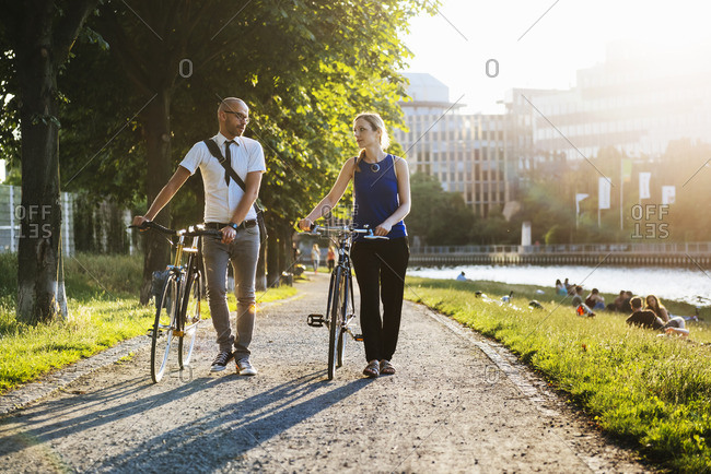Germany, Berlin, Man and woman walking with bicycles in city