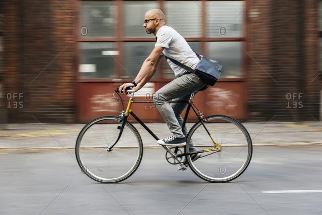 Germany, Berlin, Man cycling - Offset