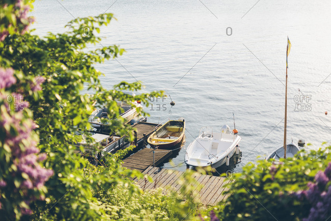 Sweden, Blekinge, Karlskrona, Bjorkholmen, Bushes and boats by dock
