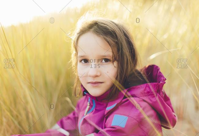 Sweden, Blekinge, Portrait of girl sitting in tall grass