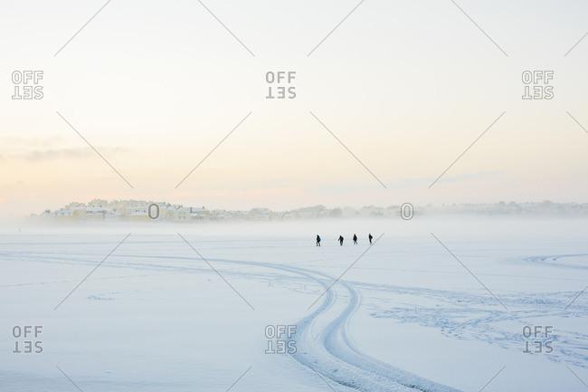 Sweden, Blekinge, Karlskrona, Borgmastarefjarden, Snowy landscape with people walking in distance