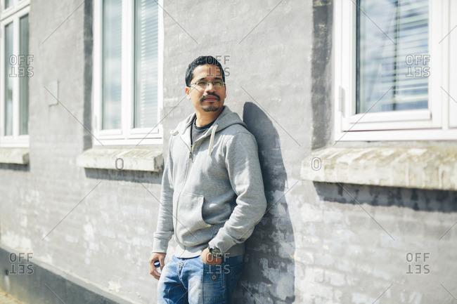 Sweden, Blekinge, Portrait of mid adult man in grey hoodie standing by house