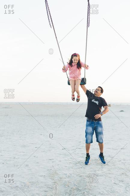 Germany, Schleswig-Holstein, Kreis Nordfriesland, Sankt Peter-Ording, Father pushing daughter on swing at beach
