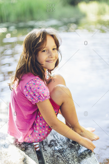 Sweden, Girl sitting on pier and smiling
