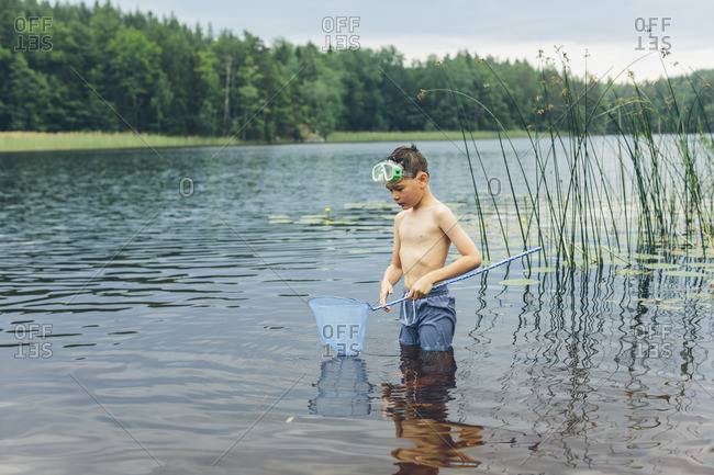 Sweden, Smaland, Mortfors, Kappemalagol, Boy (8-9-) wading and fishing