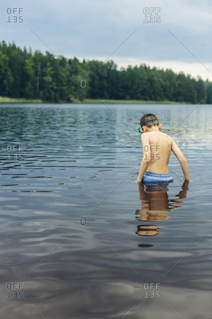 Sweden, Smaland, Mortfors, Kappemalagol, Boy (8-9-) wading in lake