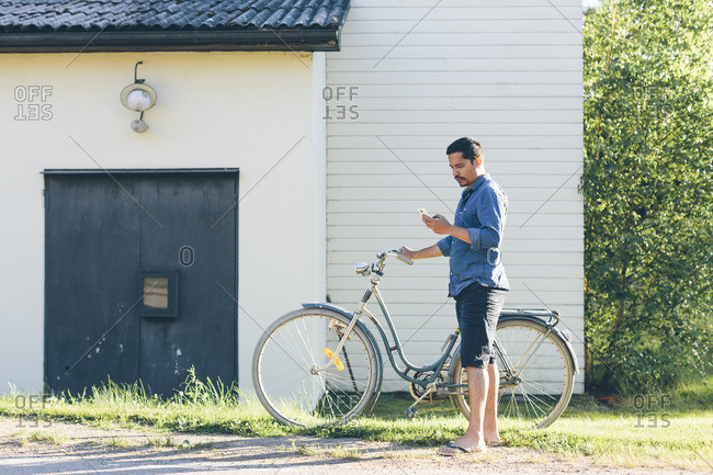 Sweden, Smaland, Mortfors, Man standing by house with bicycle and using phone