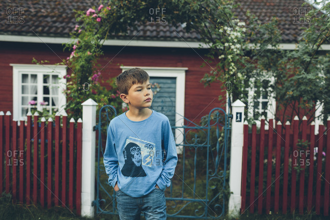 Sweden, Smaland, Mortfors, Farbo, Boy standing in front of red house