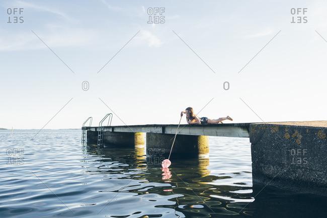 Sweden, Blekinge, Karlskrona, Salto, Girl lying on pier and fishing