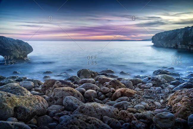 Spain, Majorca, Palma de Mallorca, Rocky coastline with sea at sunrise
