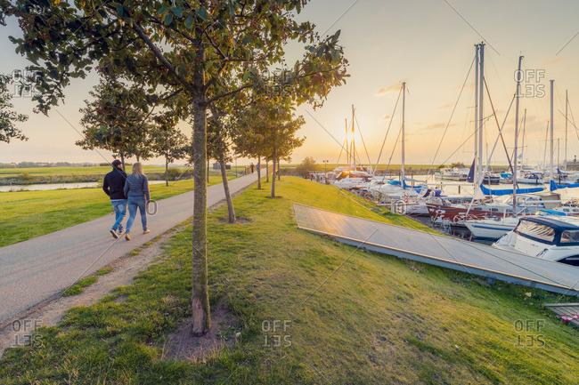 Sweden, Skane,  - September 12, 2015: Malmo, Vastrahamnen, Couple walking along promenade at sunset
