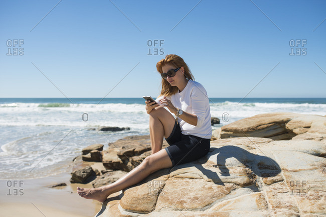 Australia, Queensland, Sunshine Coast, Maroochydore, Pincushion Island, Woman sitting on rock at seashore and checking phone