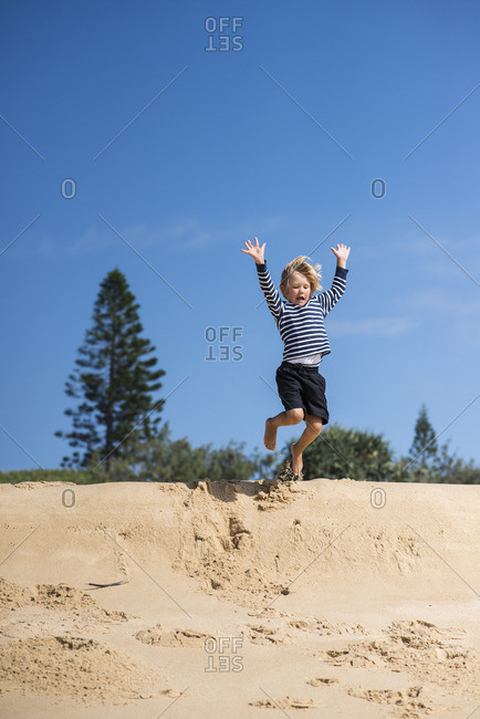 Australia, Queensland, Sunshine Coast, Buddina, Point Cartwright, Boy jumping from sand dune