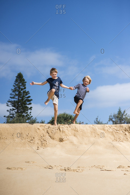 Australia, Queensland, Sunshine Coast, Buddina, Point Cartwright, Two boys (4-5, 6-7) jumping from sand dune on beach