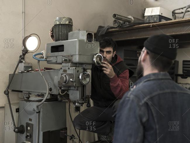 France, Men Working in metal workshop