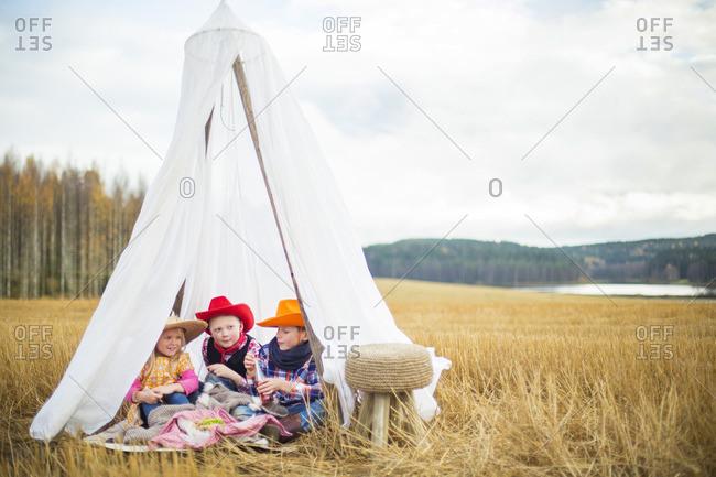 Finland, Central Finland, Aanekoski, Children wearing cowboy hats sitting in tent