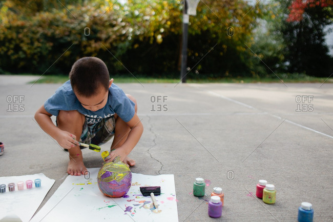 Boy covering a pumpkin with colorful paint