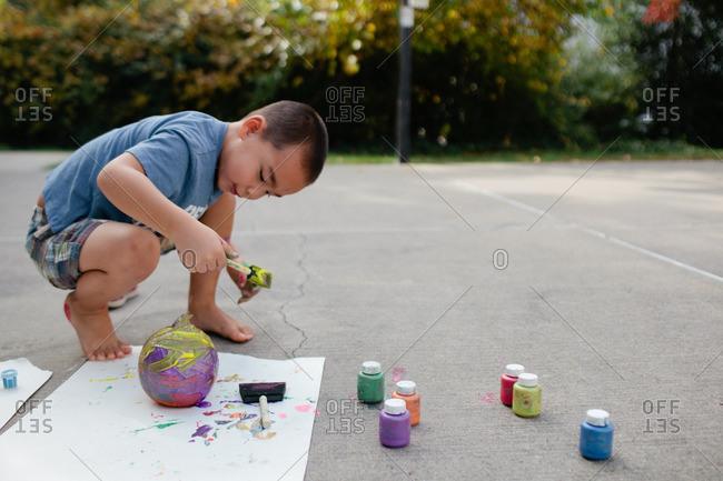 Boy painting pumpkin outdoors on basketball court